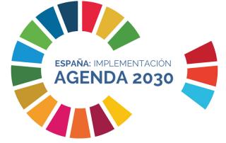 """Rueda con los idferentes colores de los Objetivos de Desarrollo Sostenible. Aprece un texto en la imagen que dice . """"España implementación Agenda 2030"""""""