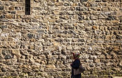 Mujer con velo en la cabeza frente a una pared de ladrillo.